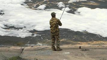jeune homme pêchant sur un lac