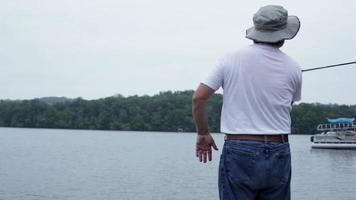 homme larguant un quai et pêcher.