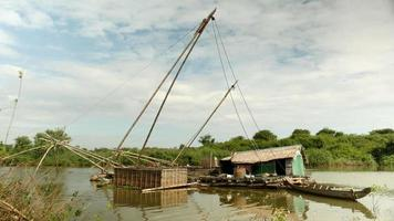House boat with chinese fishing net and bamboo fish crate on a lake