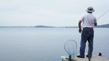 Man casting off a dock and fishing.