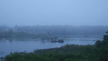 Riverside view to fisherman lifting Chinese fishing net out of water on river in foggy dawn