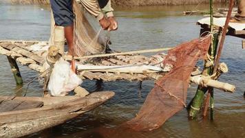 pêcheur vérifiant son filet sur une petite plate-forme en bois. il n'attrape pas de poisson seulement de l'eau de galets dans son filet