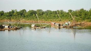 Houseboats and chinese fishing nets on river; Fisherman lifting chinese fishing net out of water