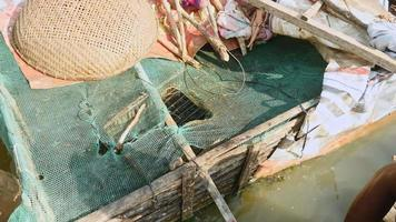close up on a fish farmer feeding fish in a bamboo crate fixed to a houseboat