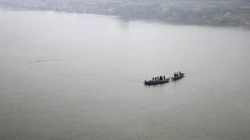 hommes sur bateau soulevant un filet hors de l'eau