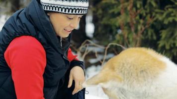 giovane donna felice e cane akita durante un'escursione invernale