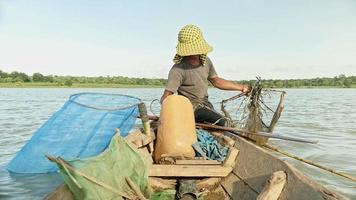 Cerca de la red de cebo del pescador de langostinos, dejándola caer más profundamente en un río y bote de remos para una nueva captura