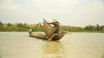 Red de cebo de pescador de camarones, dejándola caer más profundamente en un río y bote de remos para una nueva captura