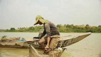 pescatore di gamberi che pesca la rete, facendola cadere più in profondità in un fiume e in barca a remi per una nuova cattura