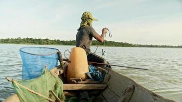 pescatore di gamberetti in piroga che tira la rete fuori dal fiume, cattura i gamberetti, esca la rete e la spinge più in profondità in un fiume