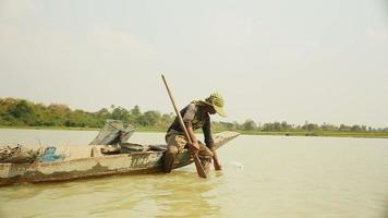 Pescador de gambas en canoa sacando la red del río, capturando camarones, cebando la red y empujándola más profundamente en un río video