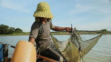 Il pescatore appende una palla da esca per la pesca dei gamberi