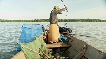 Pescador de gambas en canoa sacando la red del río, capturando camarones, cebando la red y empujándola más profundamente en un río