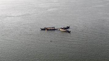 Pêcheurs dans de petits bateaux soulevant ensemble un grand filet hors de l'eau