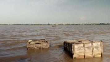 L'homme ramant son petit bateau sur la rivière tout en tirant un filet de pêche dans l'eau derrière