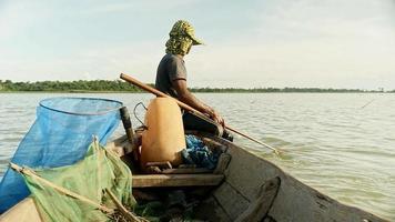 pescatore di gamberi in piroga che tira la rete di caduta dal fiume, cattura i gamberetti, esca la rete