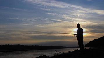 silhouette de pêcheur au coucher du soleil, casting de pêcheur