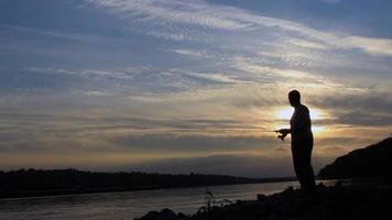 silhueta do pescador no pôr do sol, pescador lançando