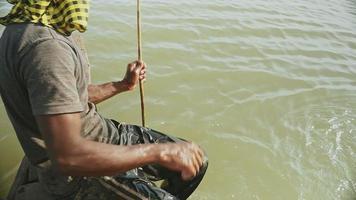 Vista superior cercana de un pescador de langostinos tirando de la red de caída del río y capturando langostinos