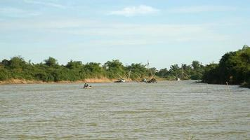 Distance view of a motorized dugout canoe on river and houseboats with fishing nets