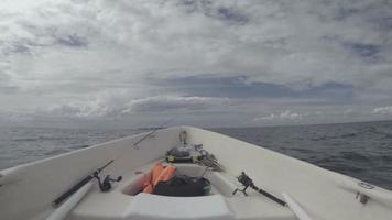 men fishing from a boat turns fishing reel
