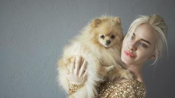 schöne blonde Frau mit ihrem Spitz lokalisiert auf grau