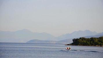 filmati di un mare e una barca con due persone che passano / una barca di pescatori che passa