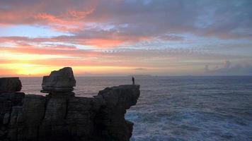 aérien: pêcheur debout au sommet de la falaise et pêche