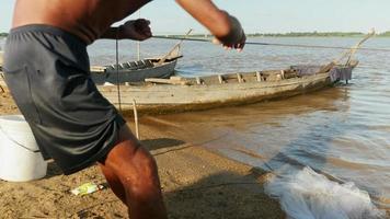 close-up de um pescador puxando uma rede de pesca da margem do rio;