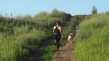 workout with dog. Young caucasian female running with siberian husky dog