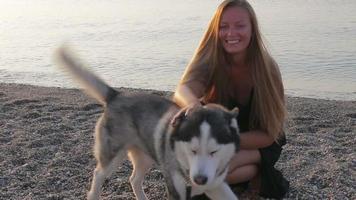 Chica husky siberiano juega con un perro en la playa