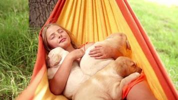 ragazza che dorme con i cuccioli in amaca video
