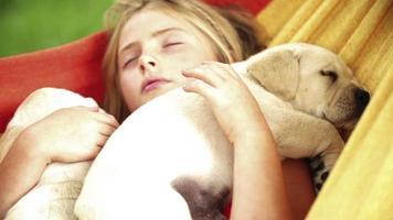 meisje slaapt met puppy's in hangmat
