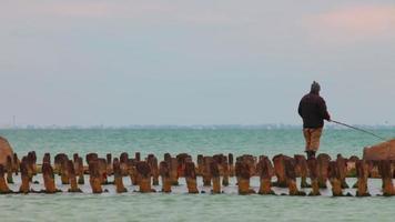 pescatore sul vecchio molo distrutto