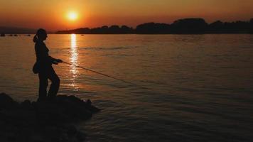Frau, die bei Sonnenuntergang fischt