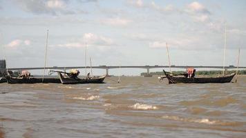 Pêcheur sur petit bateau tirant un filet de pêche dans l'eau derrière