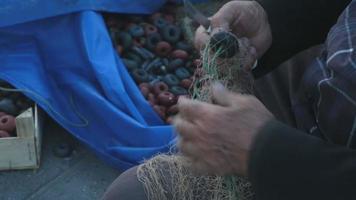 velho consertando uma rede de pesca com faca à beira-mar