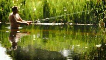 A fisher stands waist-deep in the water catching fish with a spinning