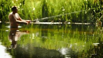 um pescador fica na água até a cintura, pegando peixes com um giro