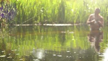 um pescador com água até a cintura tentando pegar um peixe