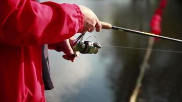 Fisherman pulls the fishing line on reel