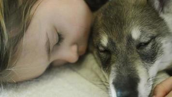 criança fingindo estar dormindo abraçando um animal de estimação