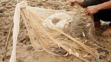 pescatore che rimuove il pesce dalla rete e lo tiene in un sacchetto di plastica