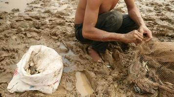 pescador retirando peixes emaranhados de sua rede e mantendo-os em um saco plástico
