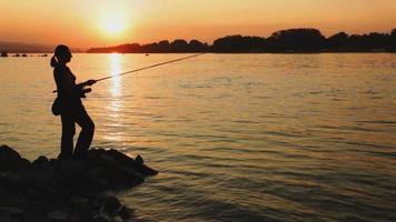 mulher pescando ao pôr do sol video