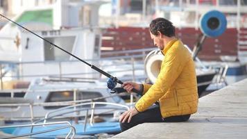 Mann sitzt auf dem Dock angeln