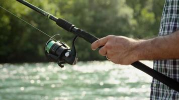 Homme avec canne à pêche à la truite sur la rivière en Italie