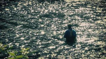 pescatore pesca a mosca nel fiume scintillante sera