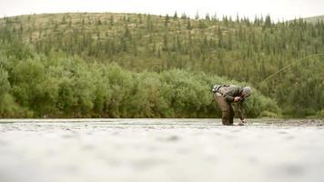 Mann, der einen Fisch in einem Fluss enthakt und loslässt