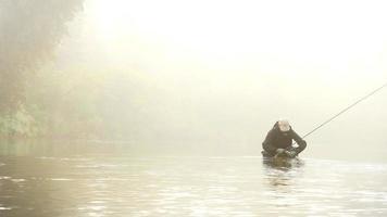 uomo che sgancia un pesce in un fiume avvolto dalla nebbia